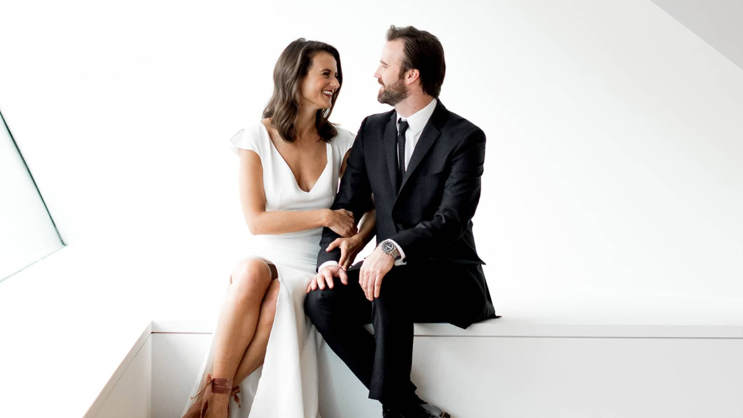 Bride and groom sit on ledge in bright, modern white room