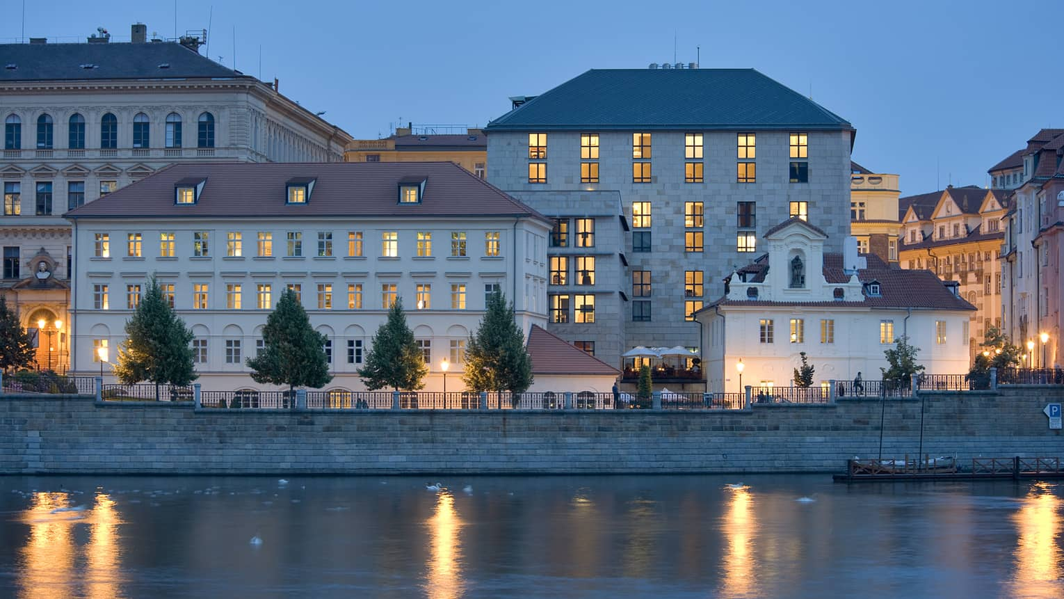 Four Seasons Hotel Prague exterior at night with lit windows, reflecting on Vltava River