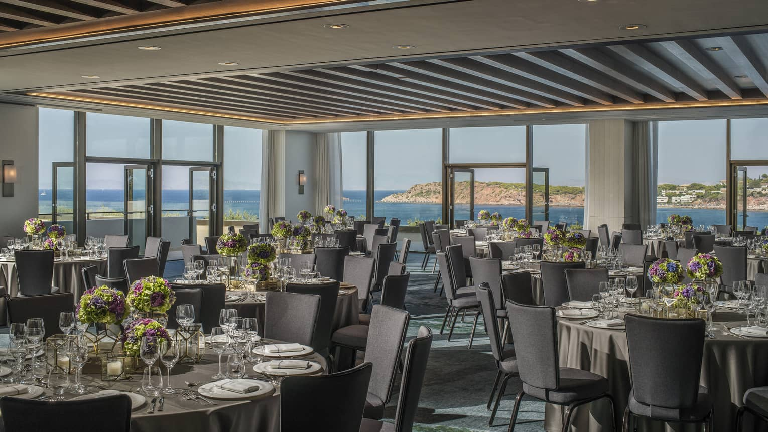 Light filled Nafsika Ballroom with round tables, grey chairs, flowers, wine glasses overlooking ocean