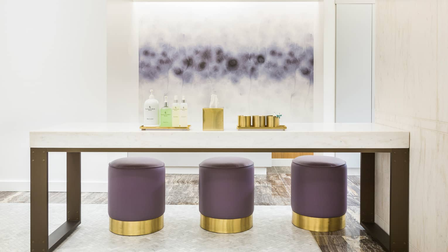 Marble treatment table in spa room, with lotions, gold tissue box and purple-and-gold stools