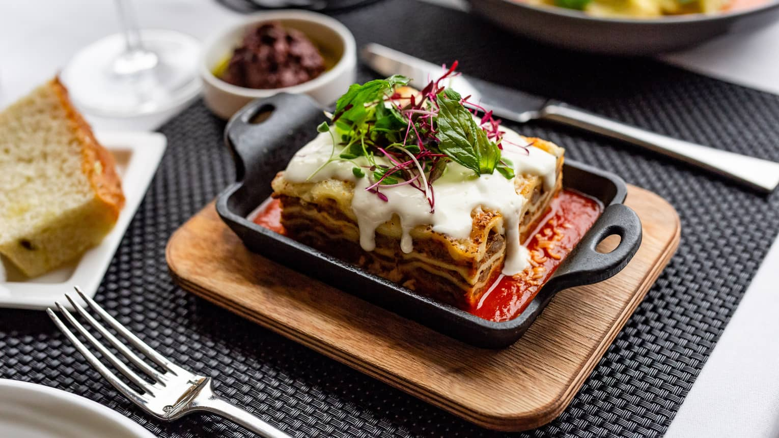 Close up of Four Seasons Houston's restaurants Quattro's House-made lasagna, slow-cooked five-layers with 44 Farms beef bolognese, ricotta-parmesan cheese fondue in a cast iron dish on top of a wooden tray