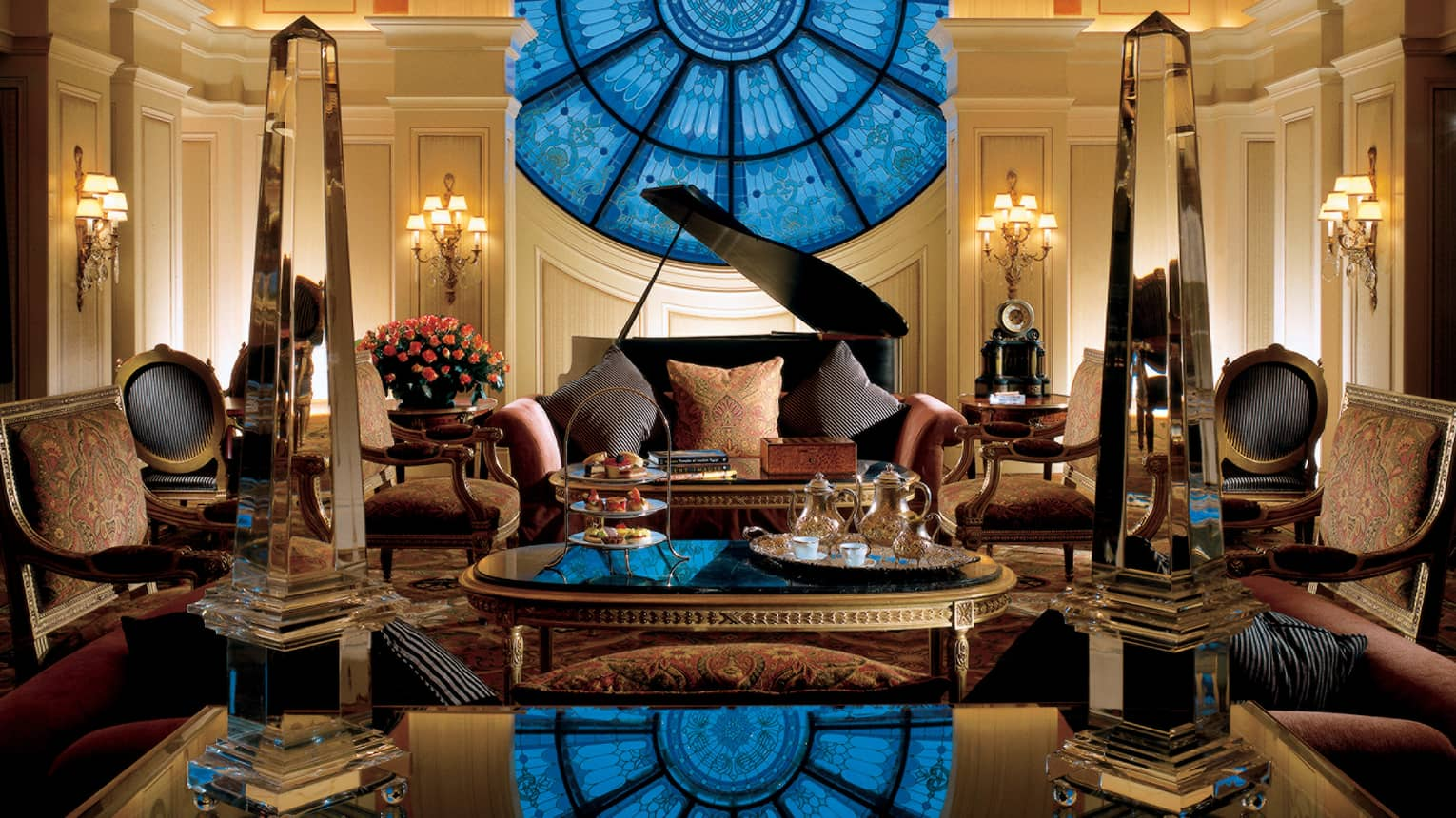 Dramatic blue circular stained-glass window over Tea Lounge grand piano, sofas