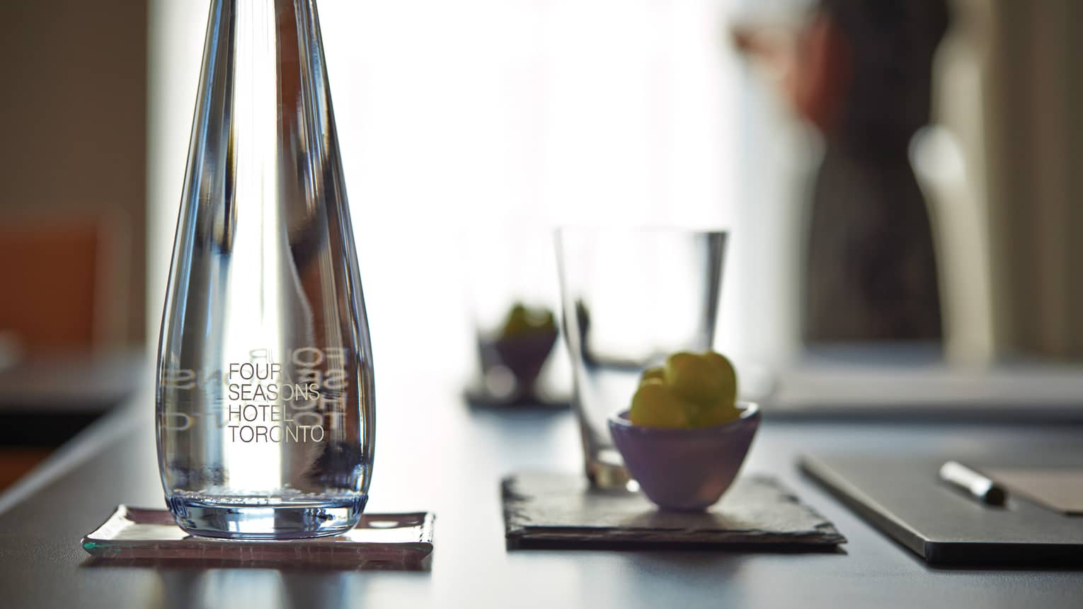 Close-up of glass water bottle, cup and agenda on meeting table
