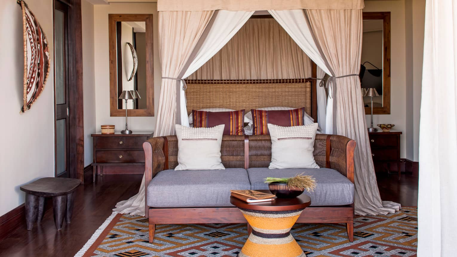 Savannah Room poster bed and canopy behind wicker loveseat, small table