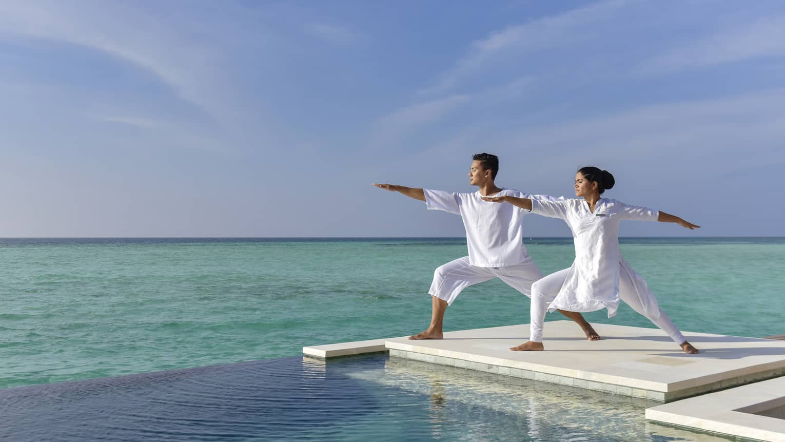 A couple dressed in all white does yoga on a white dock over the sea