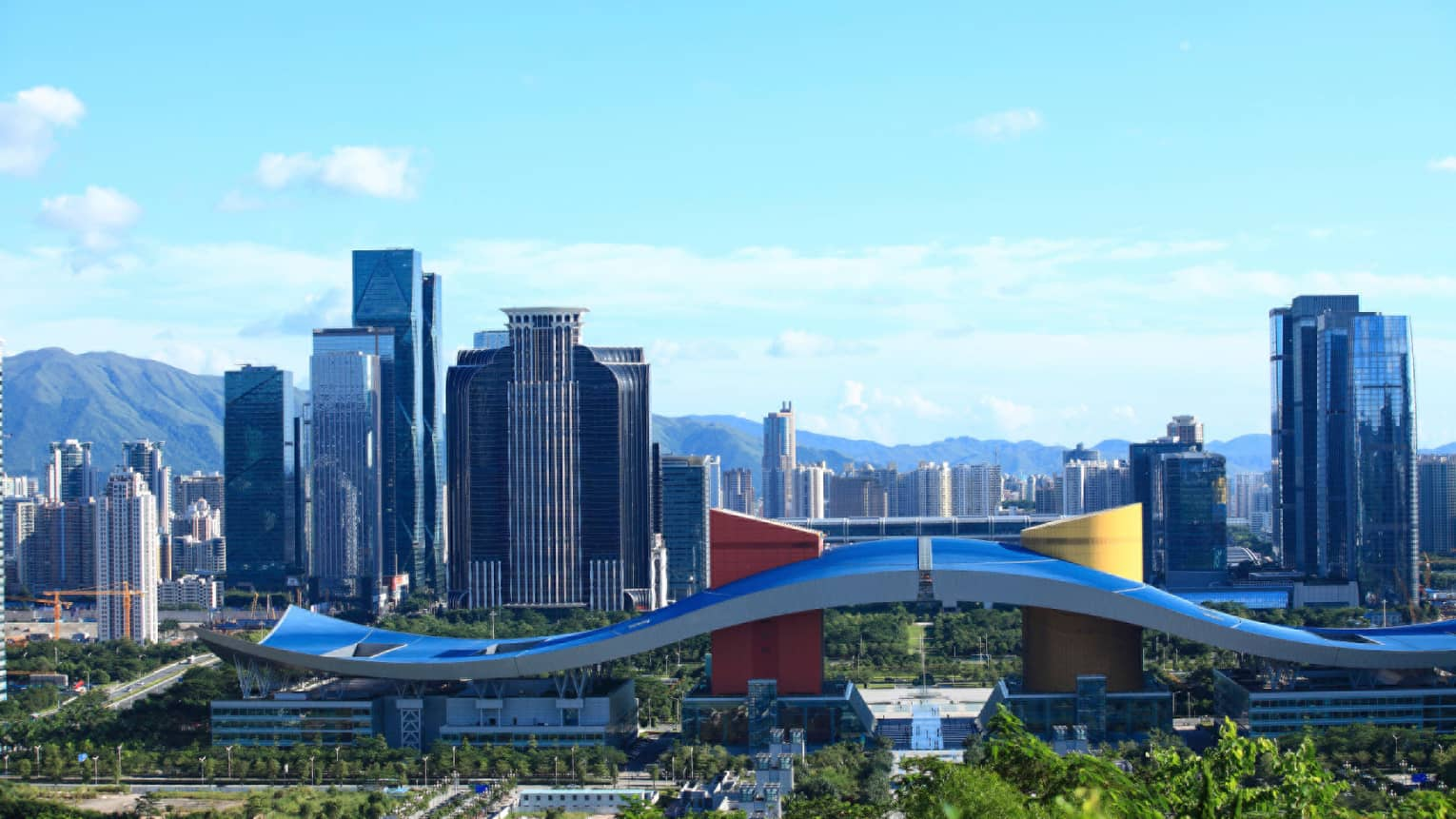 View over Shenzhen curved city hall roof, business district high rise buildings against mountains