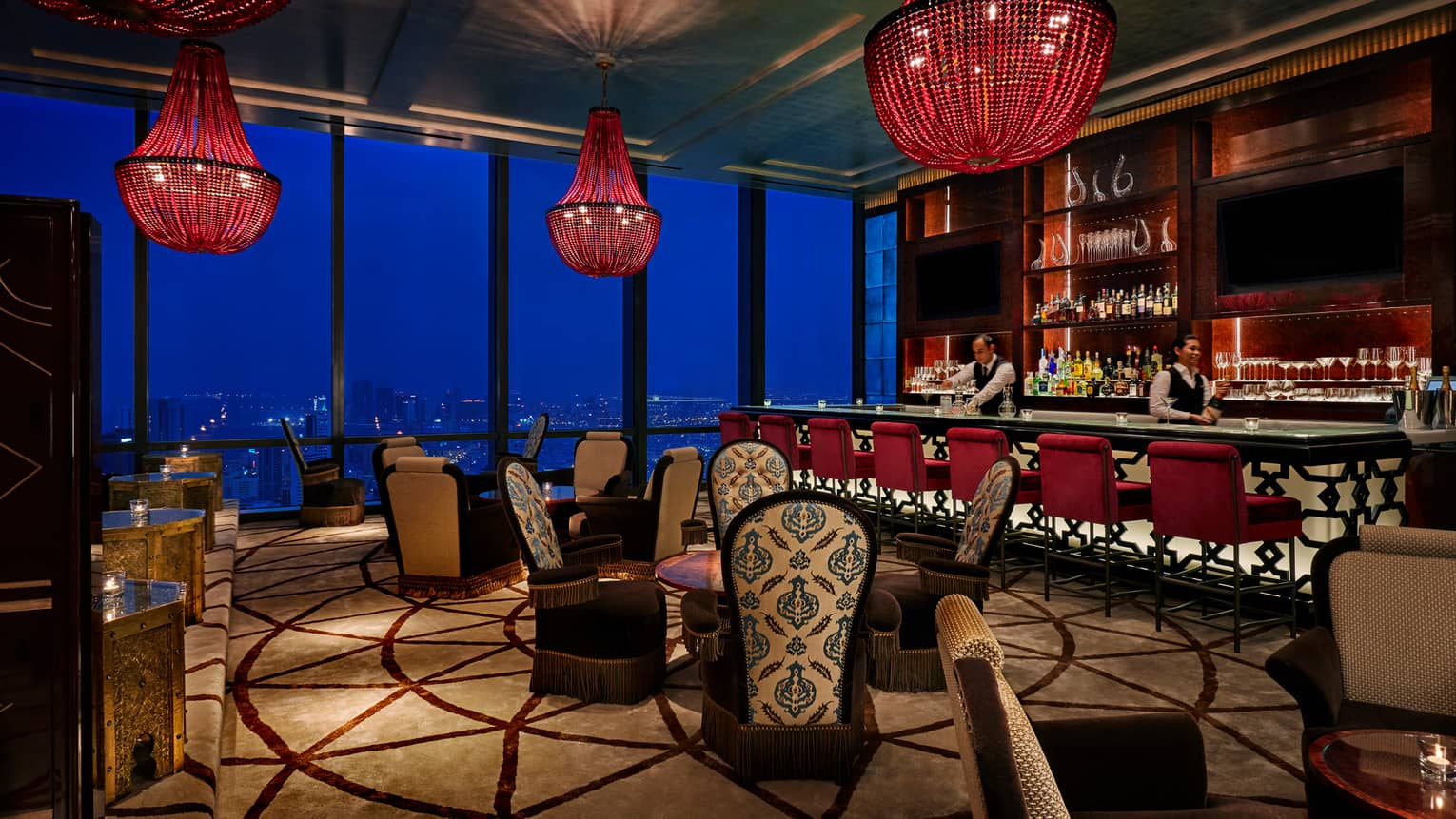 Dimly-lit Blue Moon lounge with large red beaded chandeliers, high-back plush chairs with decorative prints, bar