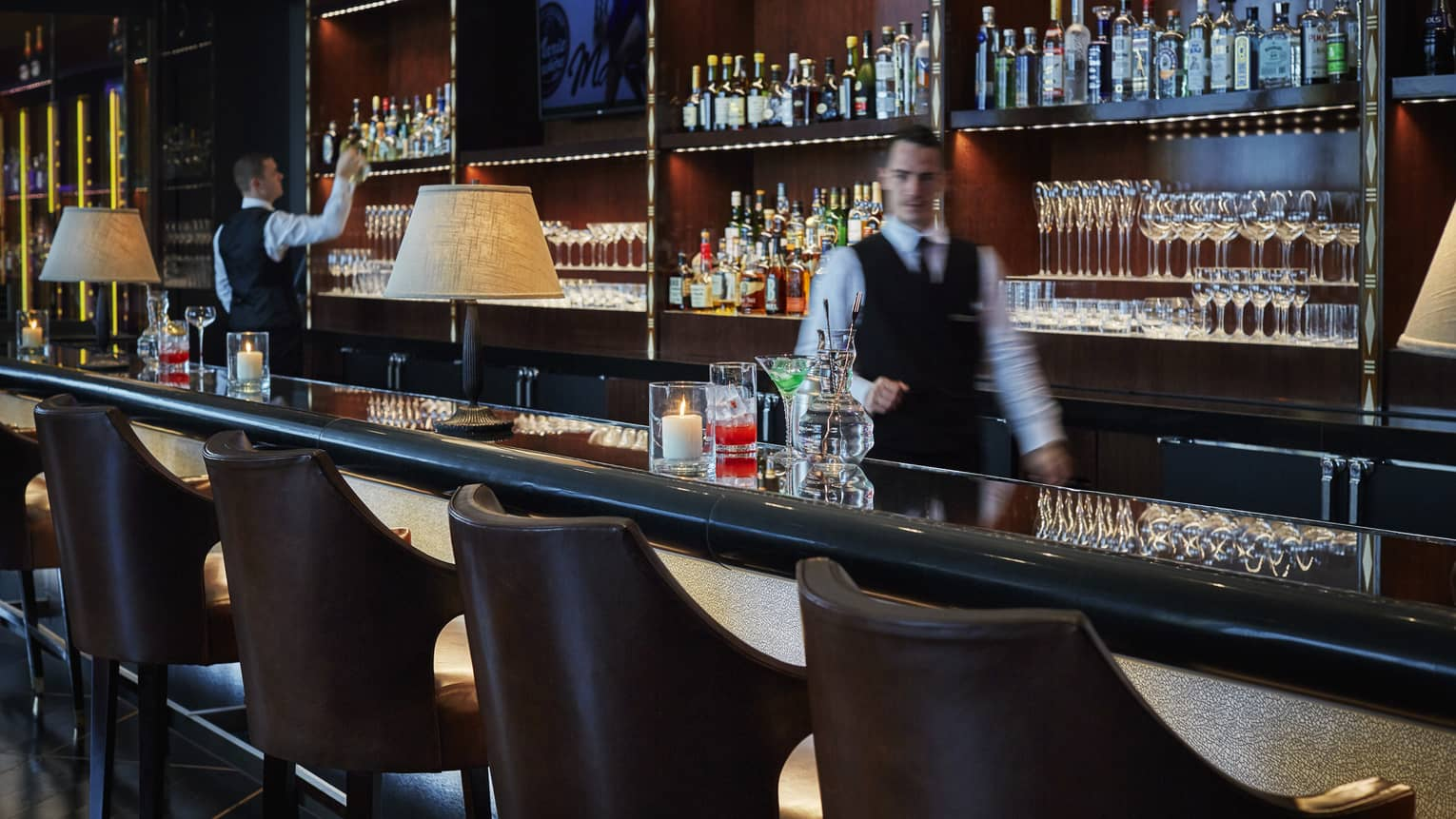 Bartender in black vest, white shirt, walks behind dimly-lit bar lined with leather bucket stools
