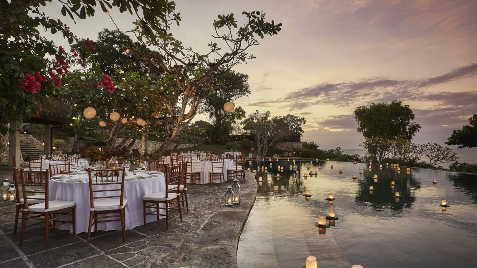 Pool Terrace banquet dining tables by candles floating on water at sunset