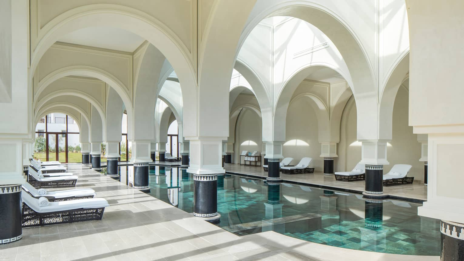 Arched white pillars, soaring ceilings over sunny indoor swimming pools, lounge chairs