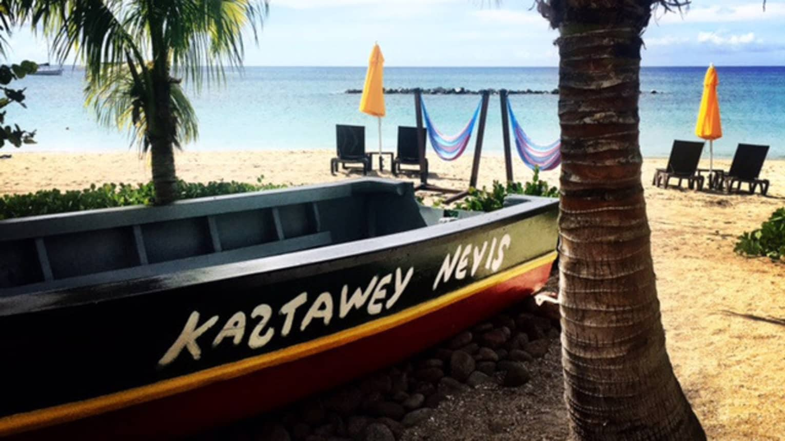 Boat with Kastaway Nevis name on beach beside palm tree near hammocks