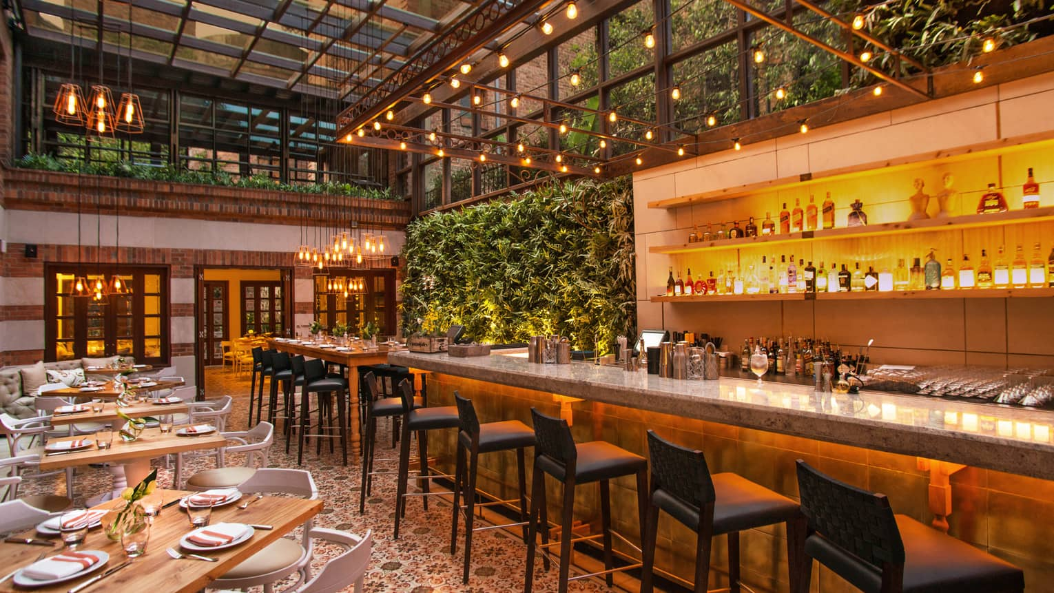 Castanyoles dining room and bar with high ceilings, Spanish-style decor, living walls with lush green plants, patio lights
