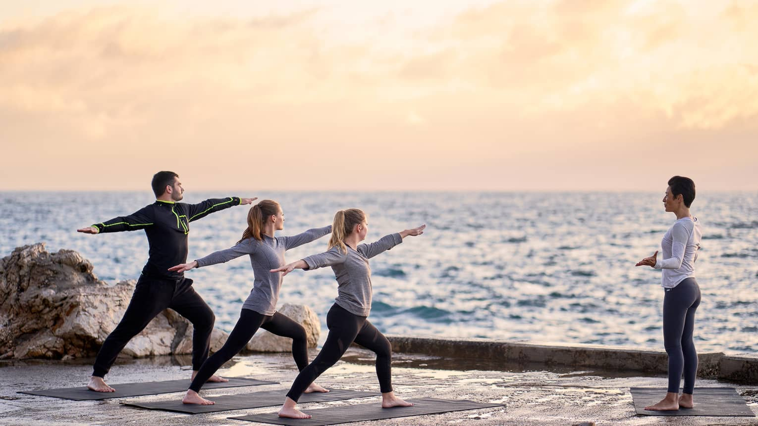 Three people in warrior yoga pose and coach standing at sea's edge at sunrise