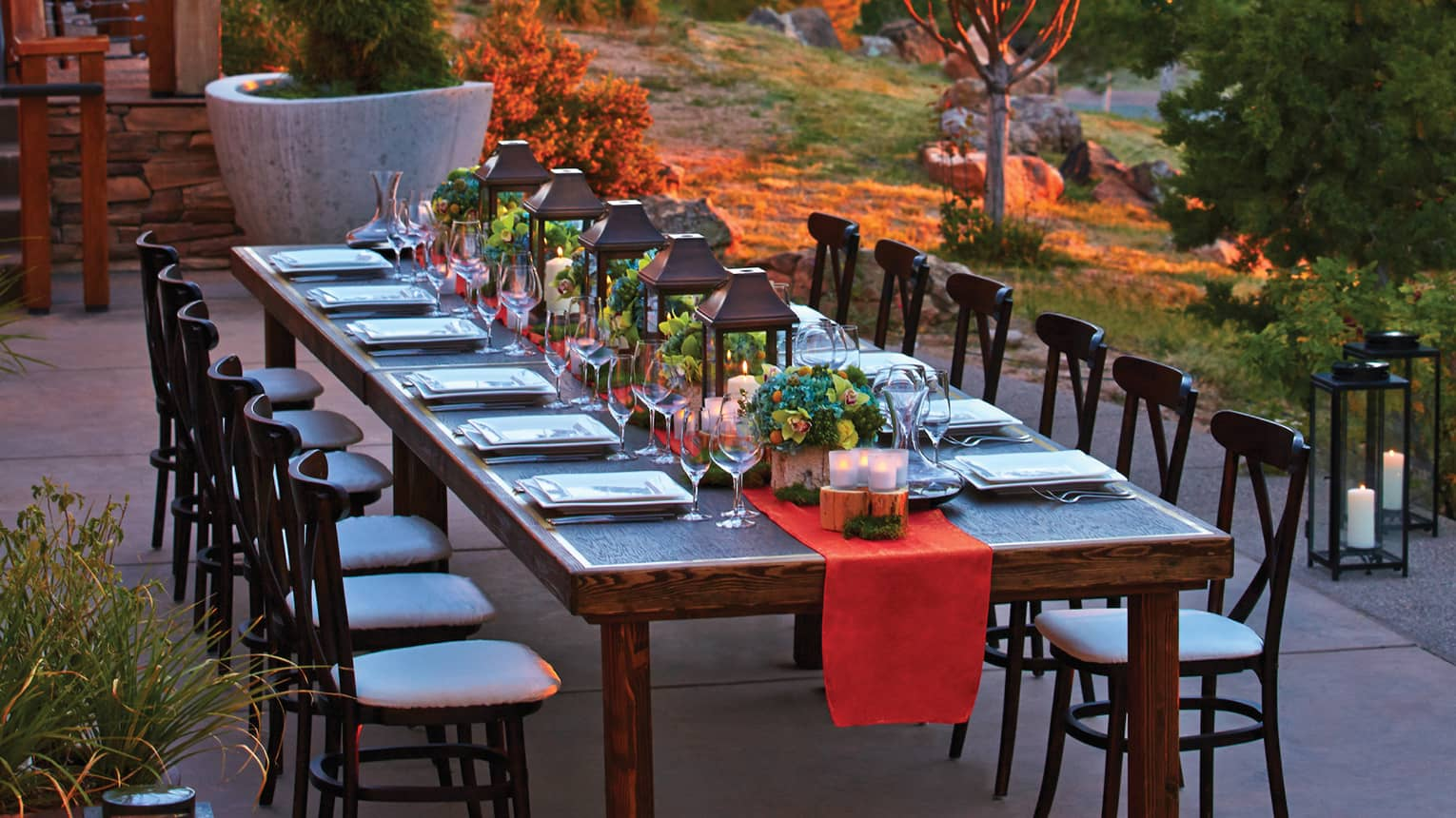Long wooden table set with red table runner, lanterns, flowers, wine glasses on outdoor terrace at dusk
