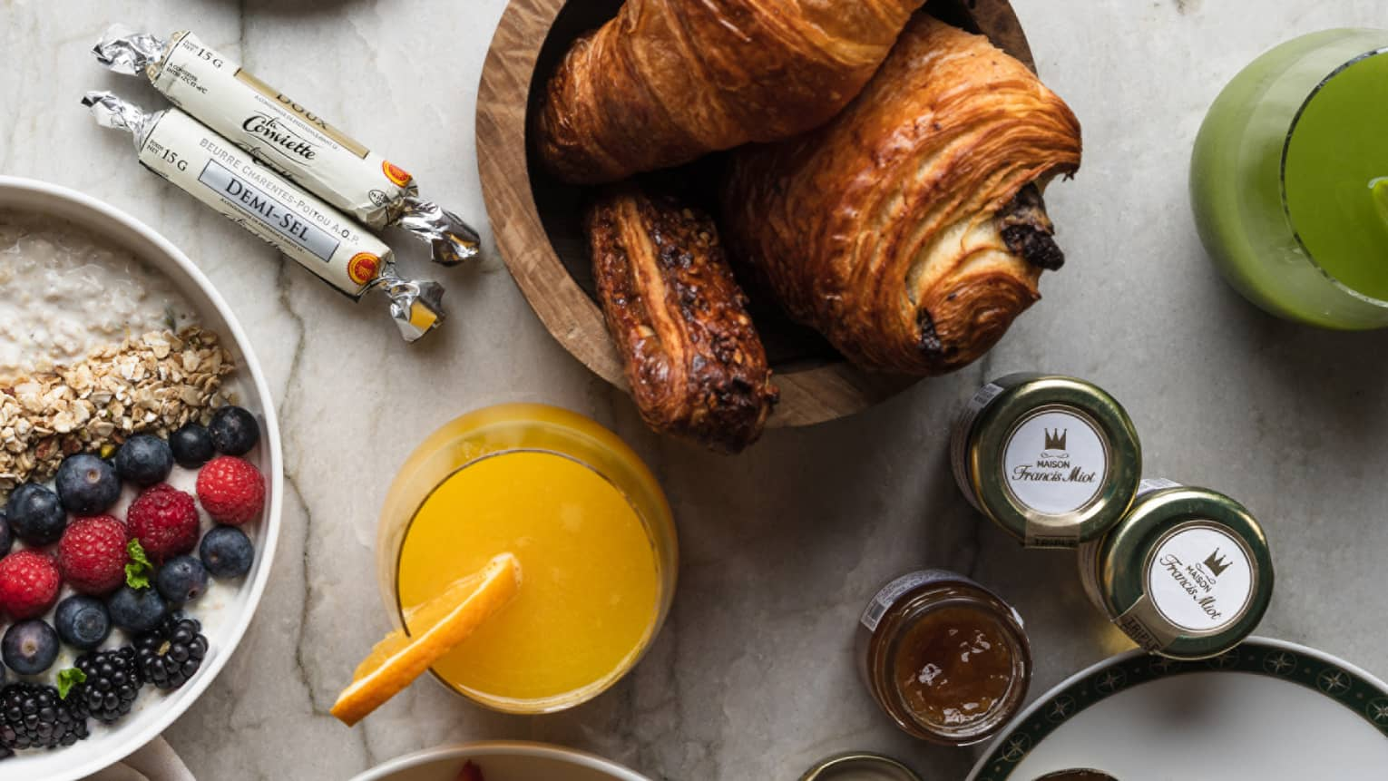Overhead shot of croissants, orange juice, jam assortment and other brunch items on a marbled table top
