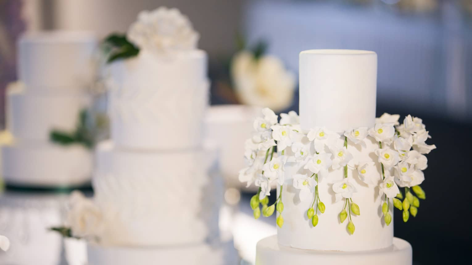 Three-tiered wedding cakes are each garished with white florals