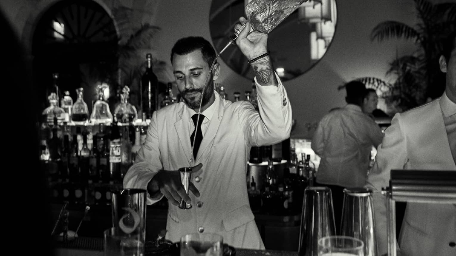Black & white shot of a bartender pouring liquor into a shot glass
