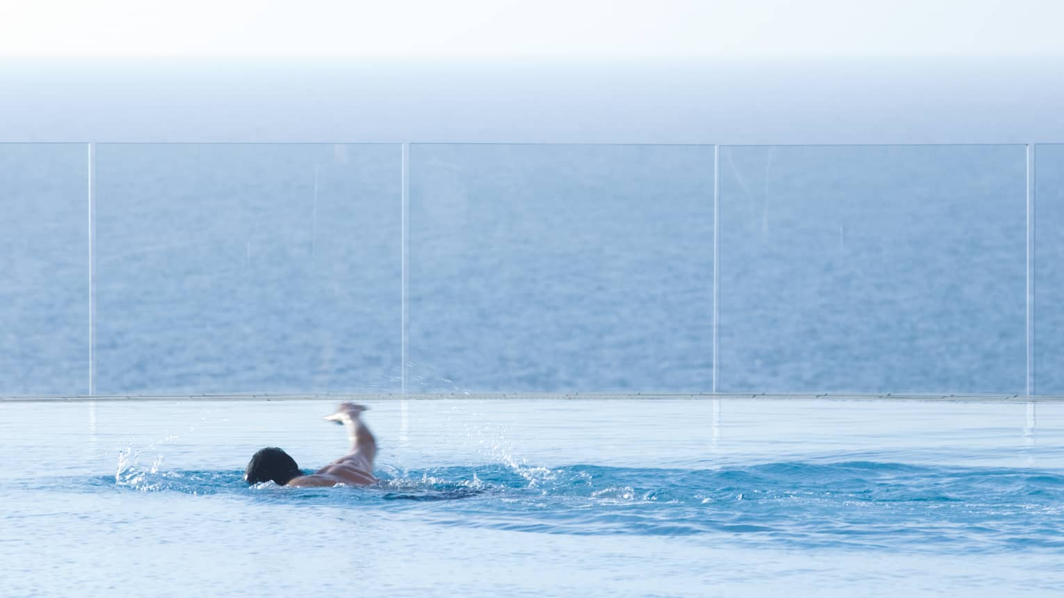 Man swimming laps in blue water of infinity swimming pool overlooking sea