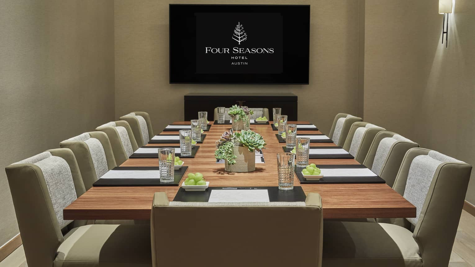 Bouldin Creek meeting room with long boardroom table, screen with Four Seasons logo
