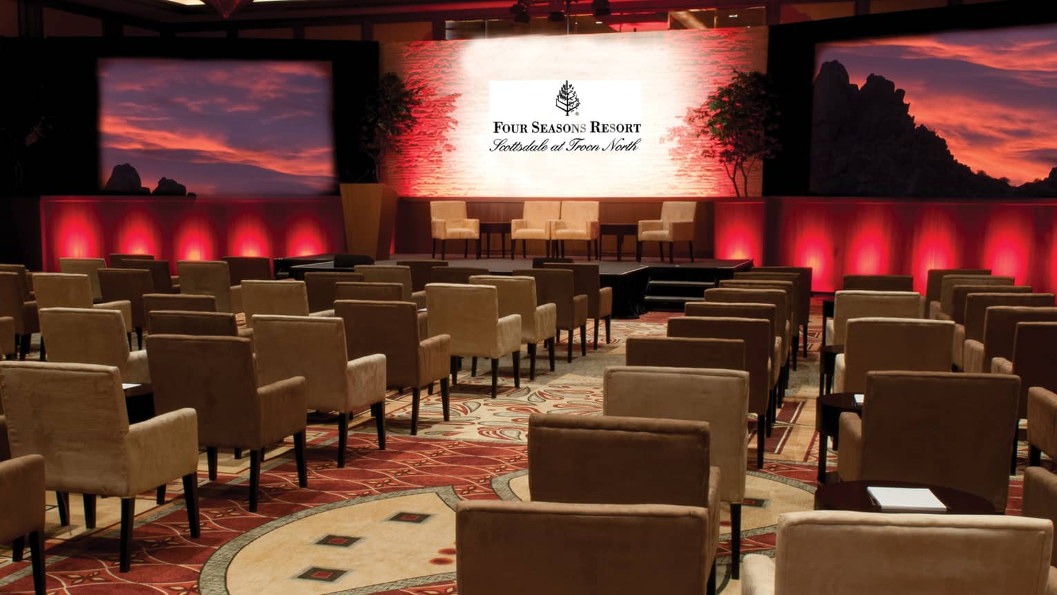 Pinnacle Ballroom conference with rows of chairs  facing large screen, projected red sunset image