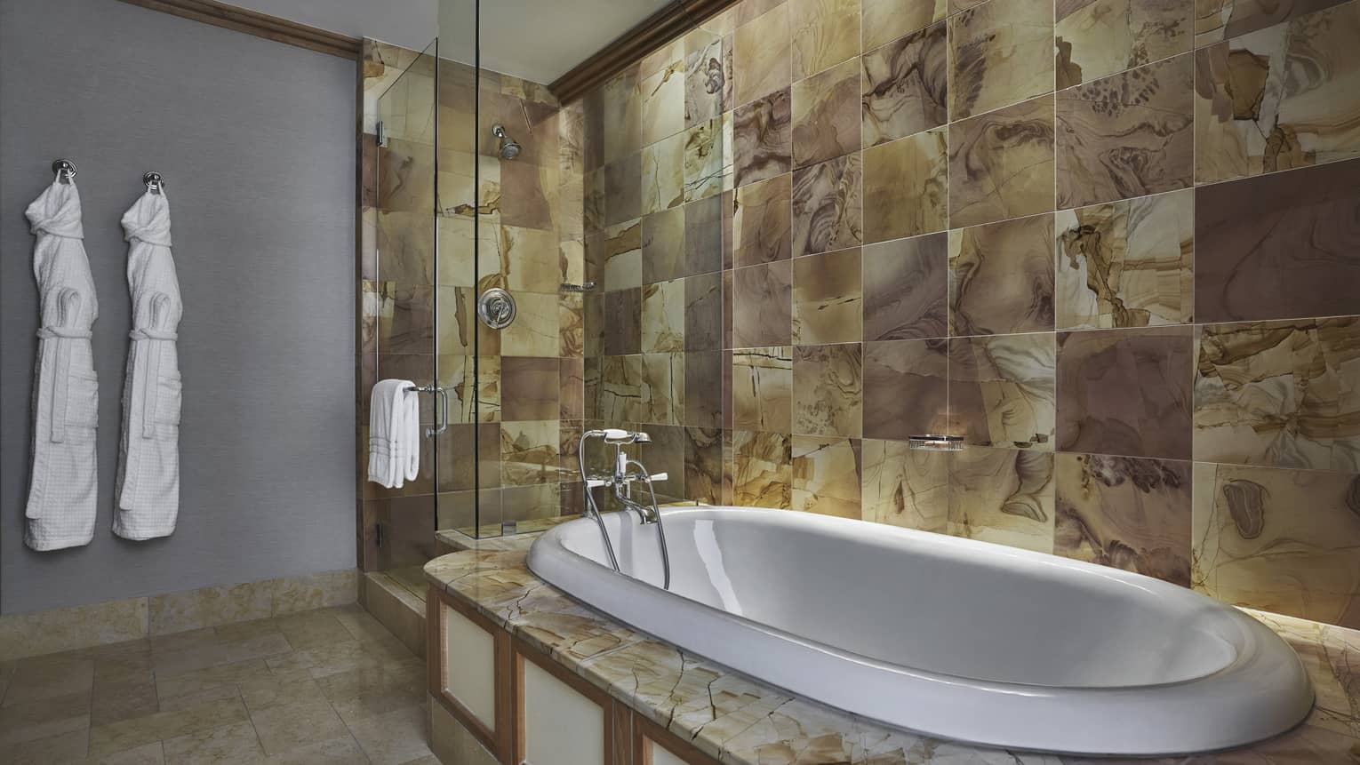 Tiled bathroom with a soaking tub and separate glass-enclosed shower