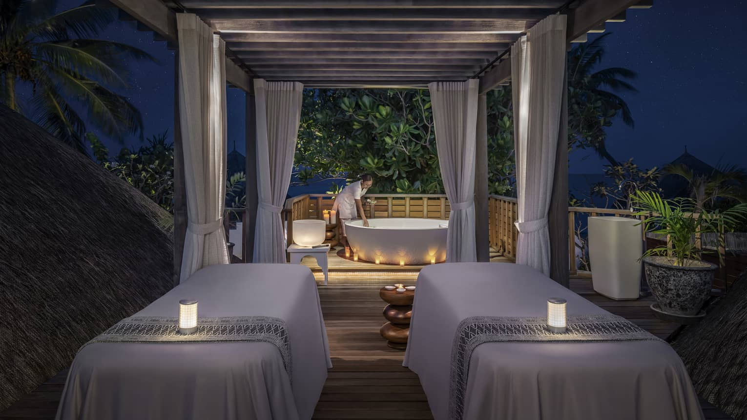 Couples massage beds with glowing candles at outdoor spa pavillion at night