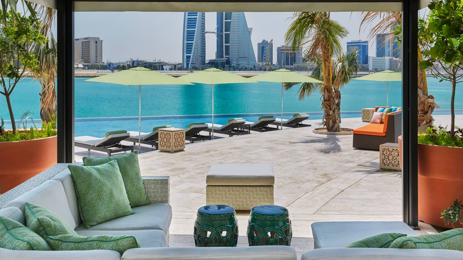 Plush outdoor patio seating and pillows under cabana, infinity swimming pool and Arabian Gulf in background