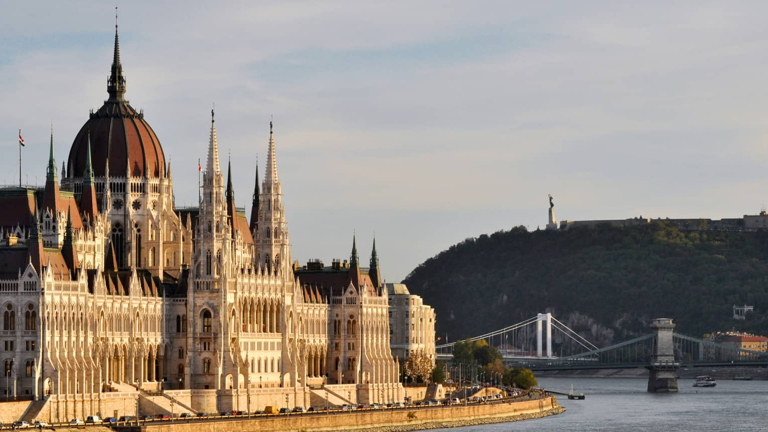 Exterior view of sun shining on the Hungarian Parliament Building beside the Chain Bridge