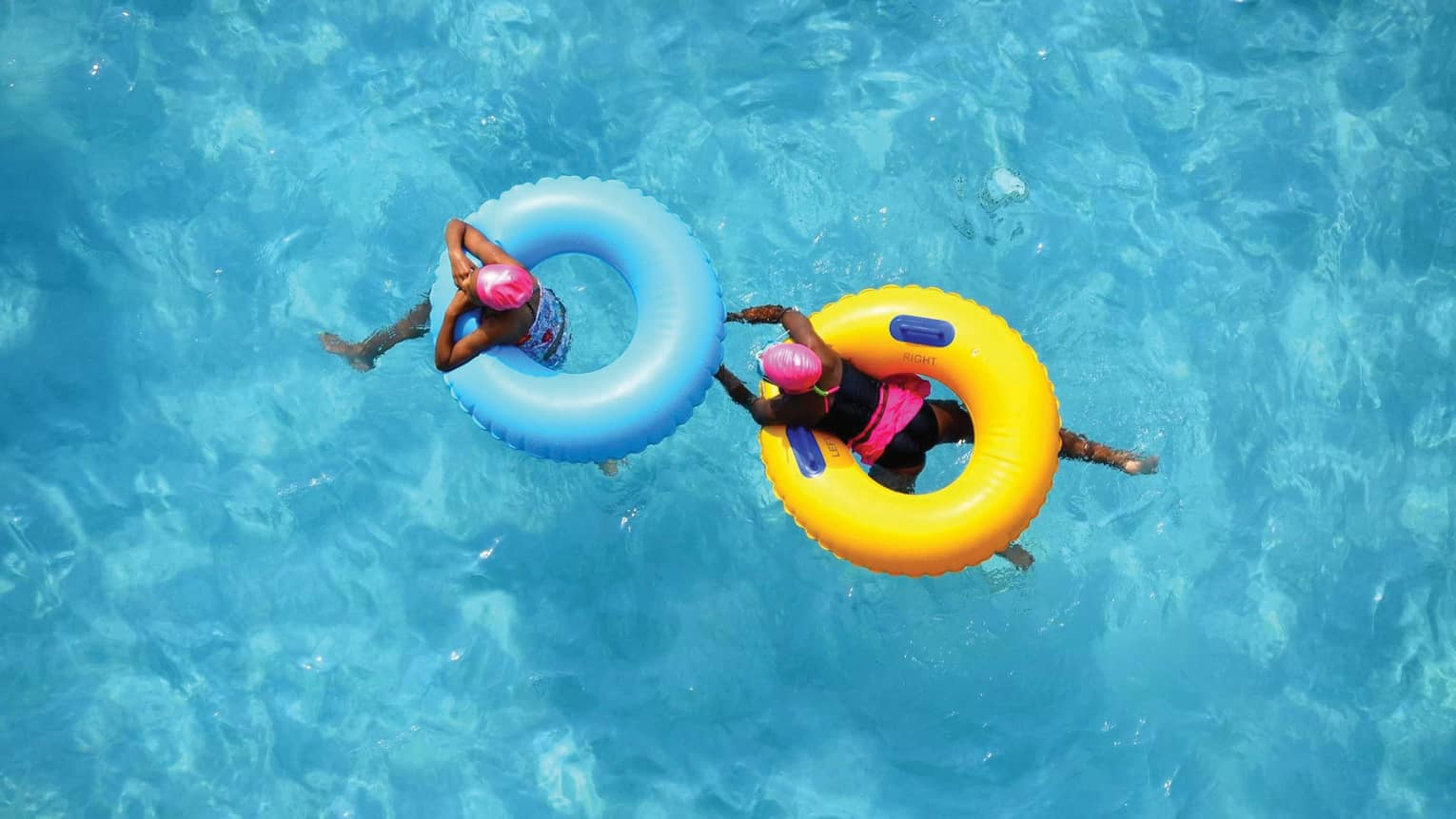 Aerial view of two swimmers in pink caps floating in blue and yellow inner tubes