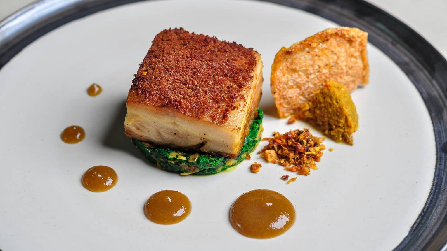 Babi Guling pork belly dish with crusted spice rub, sauteed pumpkin, dabs of orange sauce on white plate,