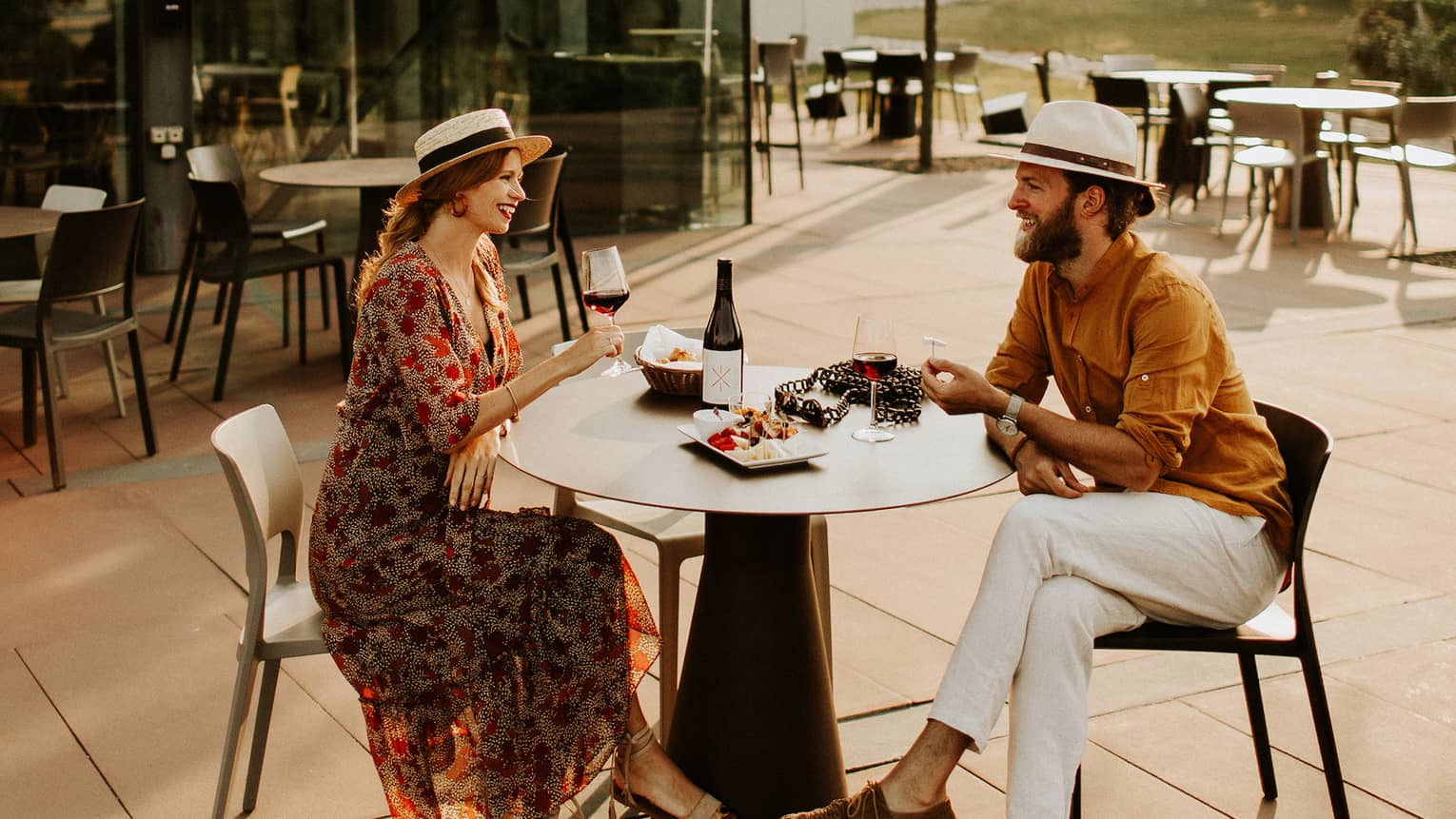 Couple wearing hats sit at outdoor table with plate of food, drinking red wine
