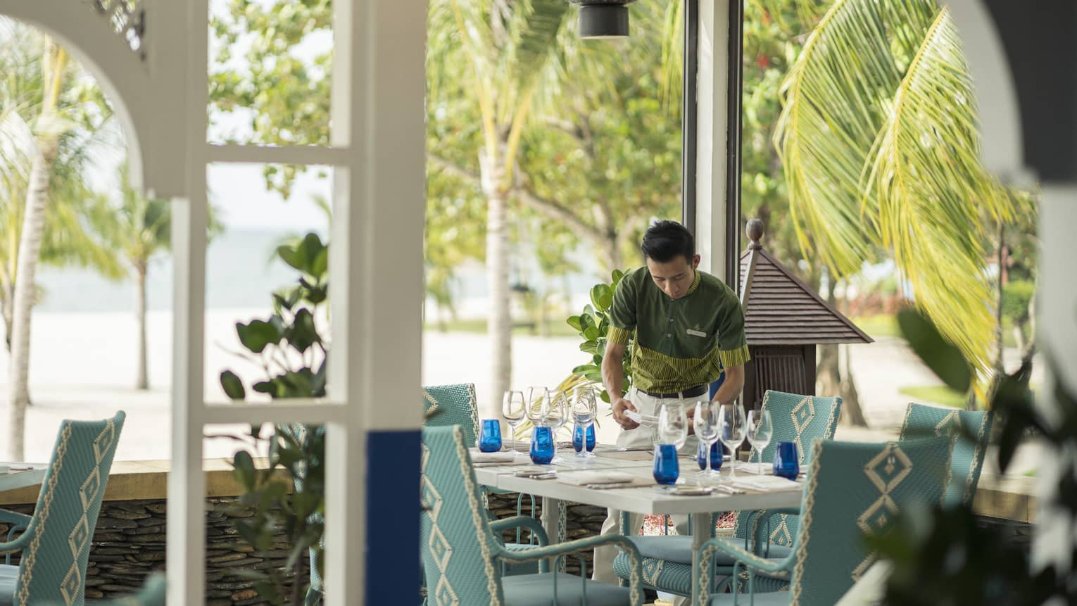 A chef sets the table in Upper Serai Restaurant