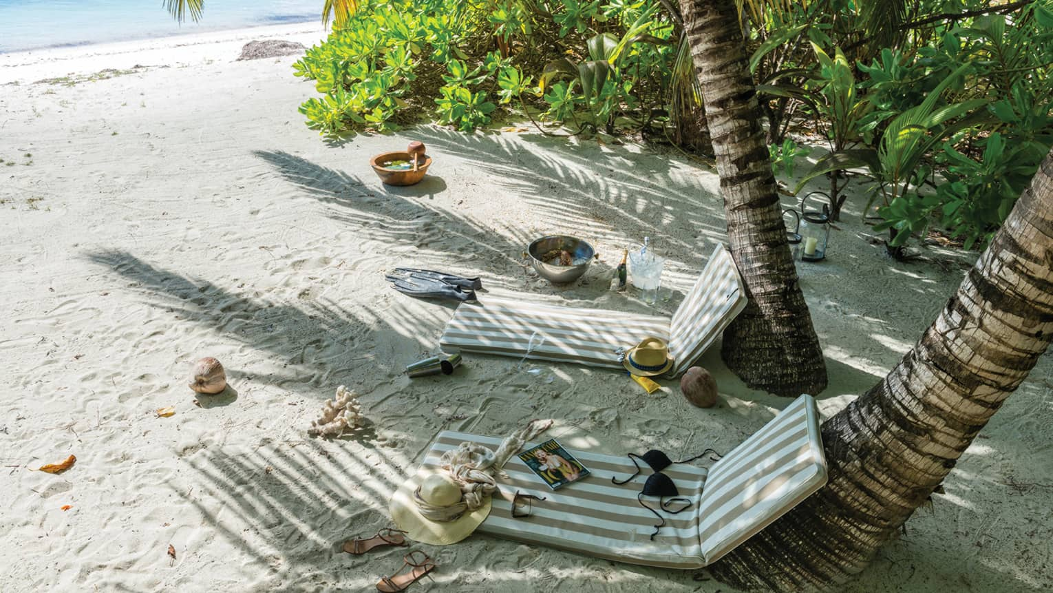 Striped patio chair cushions lean up against palm tree trunks on sandy beach, magazines, hats on ground