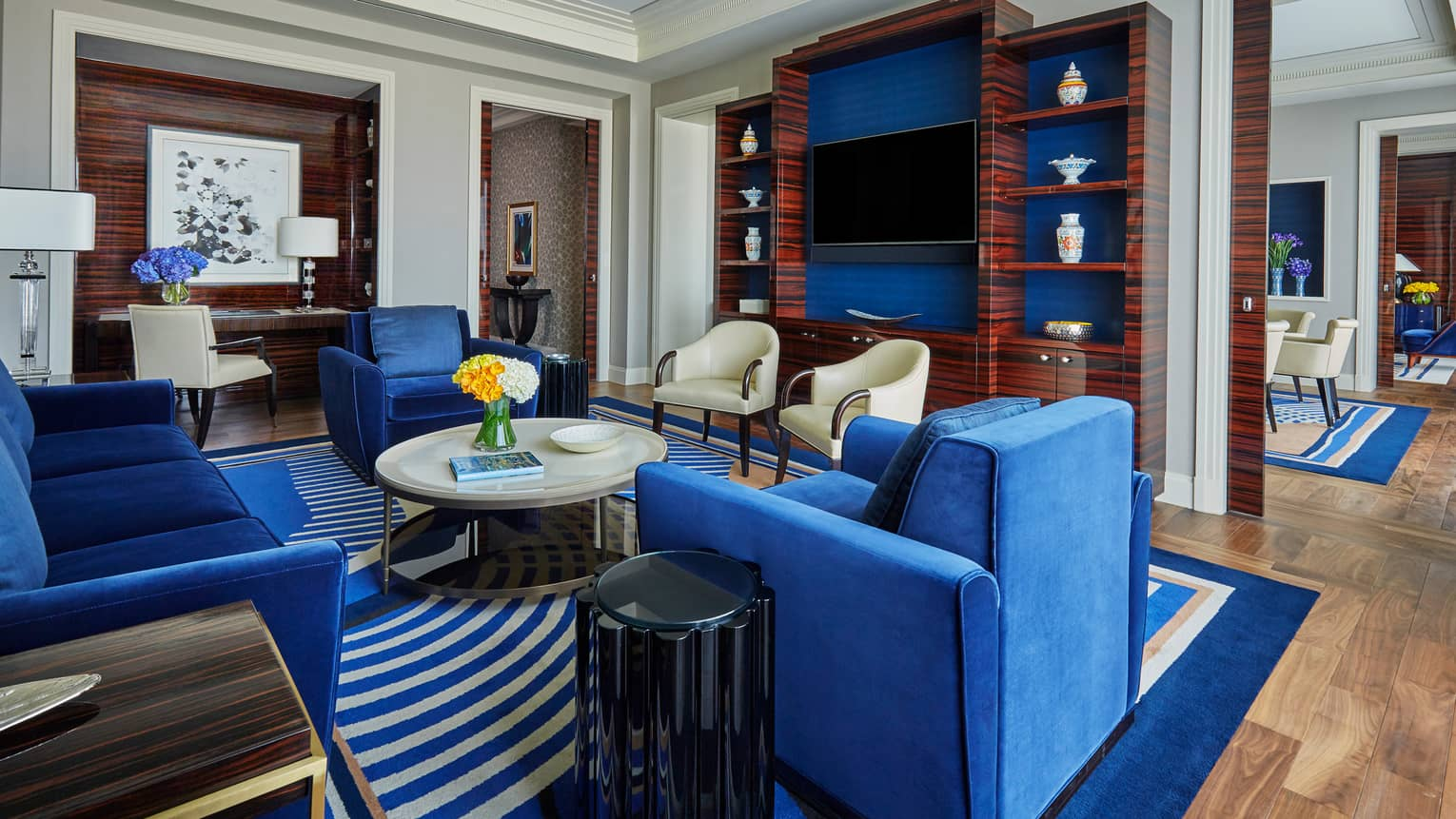 State Suite living room with plush blue sofa, armchairs, round coffee table, TV wall cabinet