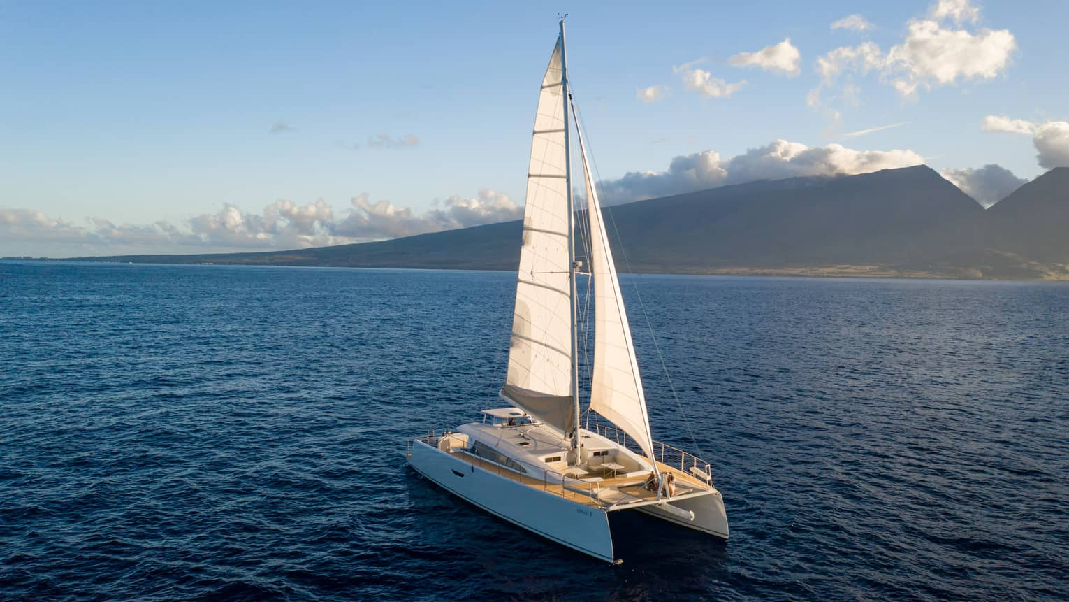 Catamaran sailing on the open water against mountain backdrop