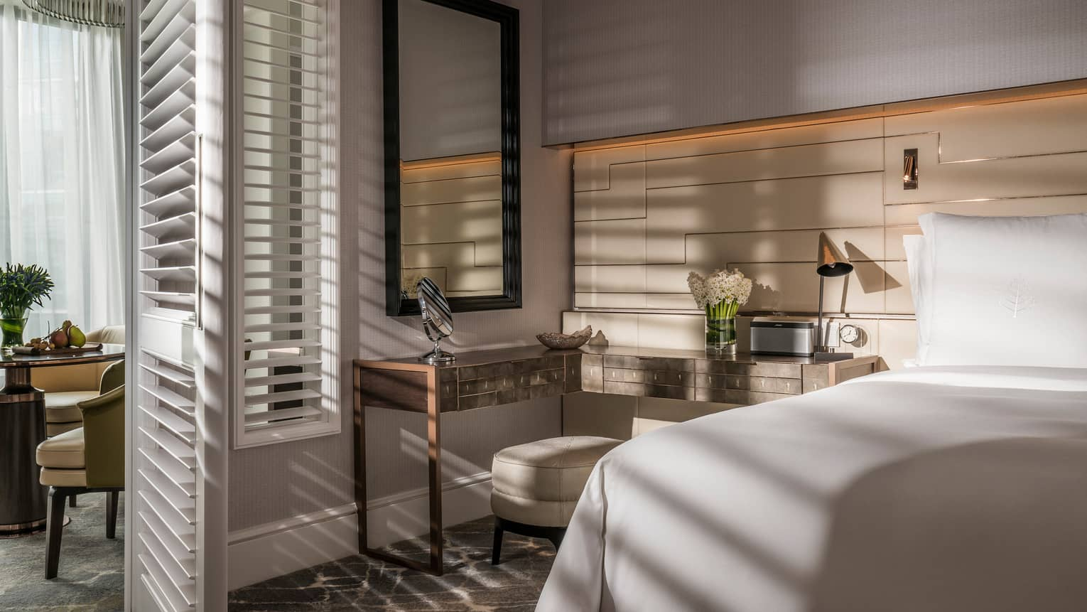 Sun streams into bedroom through tall white California shutters on dining room wall