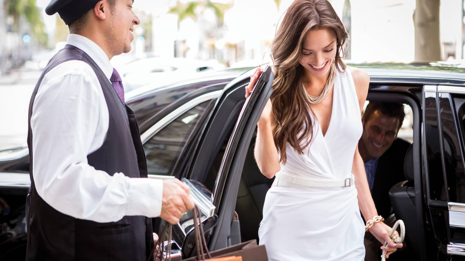 Woman wearing white dress steps out of luxury car, doorman holds door