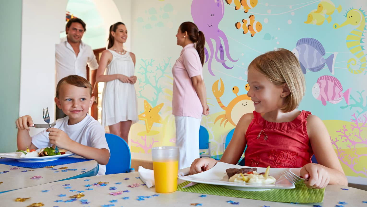 Two smiling young children at table with plates of lunch, glass of orange juice, parents and staff in front of colourful sea mural