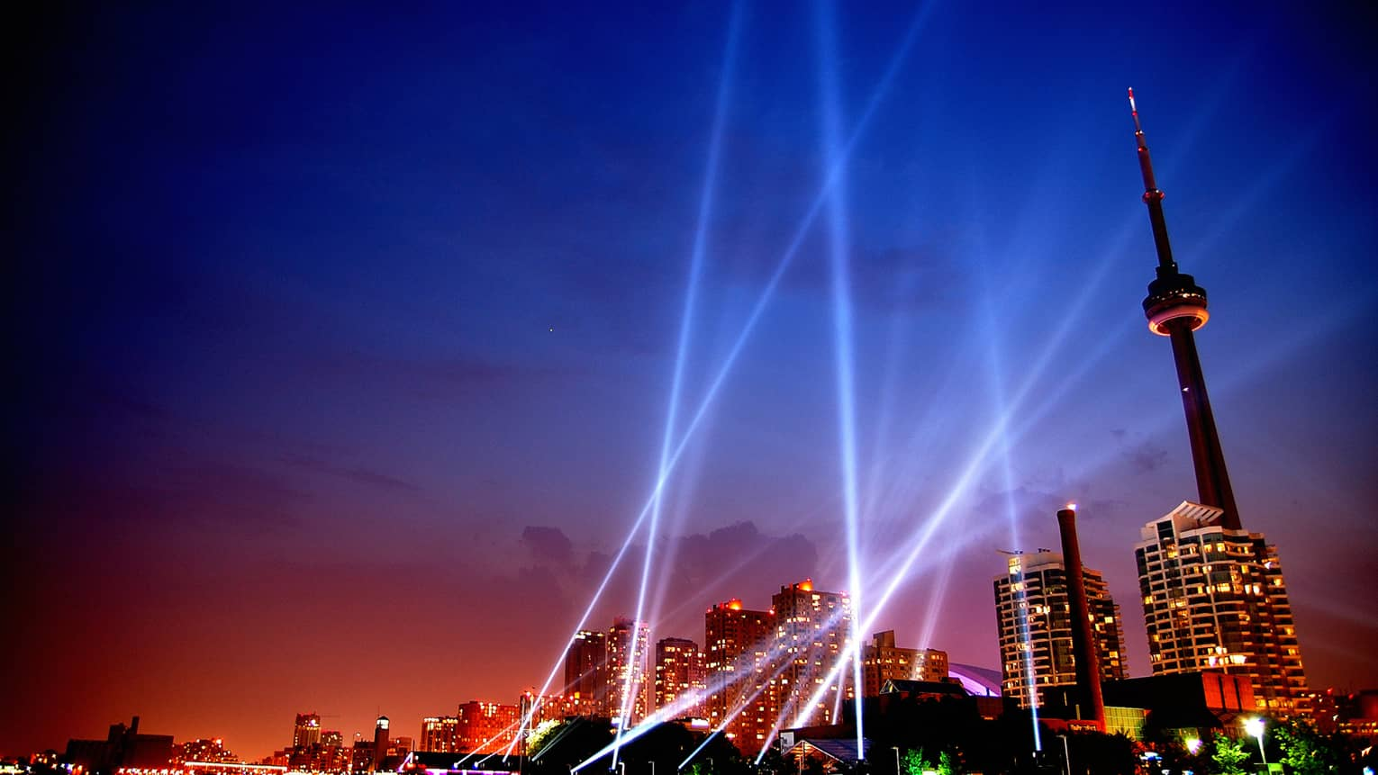 Laser beams in the sky toward colourful lights of condo buildings, CN Tower at sunset