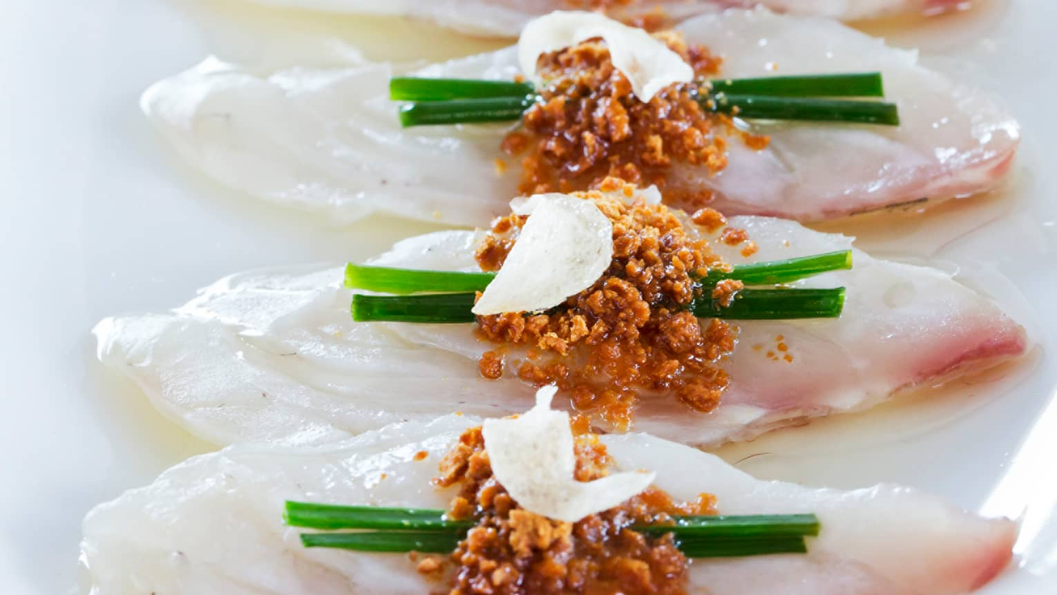 Seabass Sashimi pieces in a row, each one topped with two green onion spears, miso crush