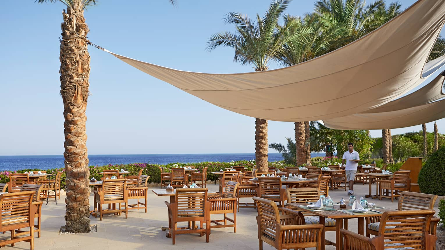 Canvas canopies attached to palm tree extend over outdoor Reef Grill patio, sea in background