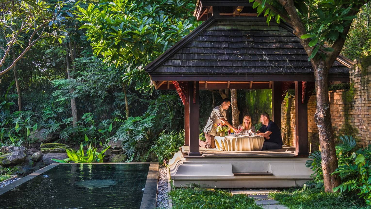 Hotel staff pours fresh juice for couple at private patio dining table under wood gazebo