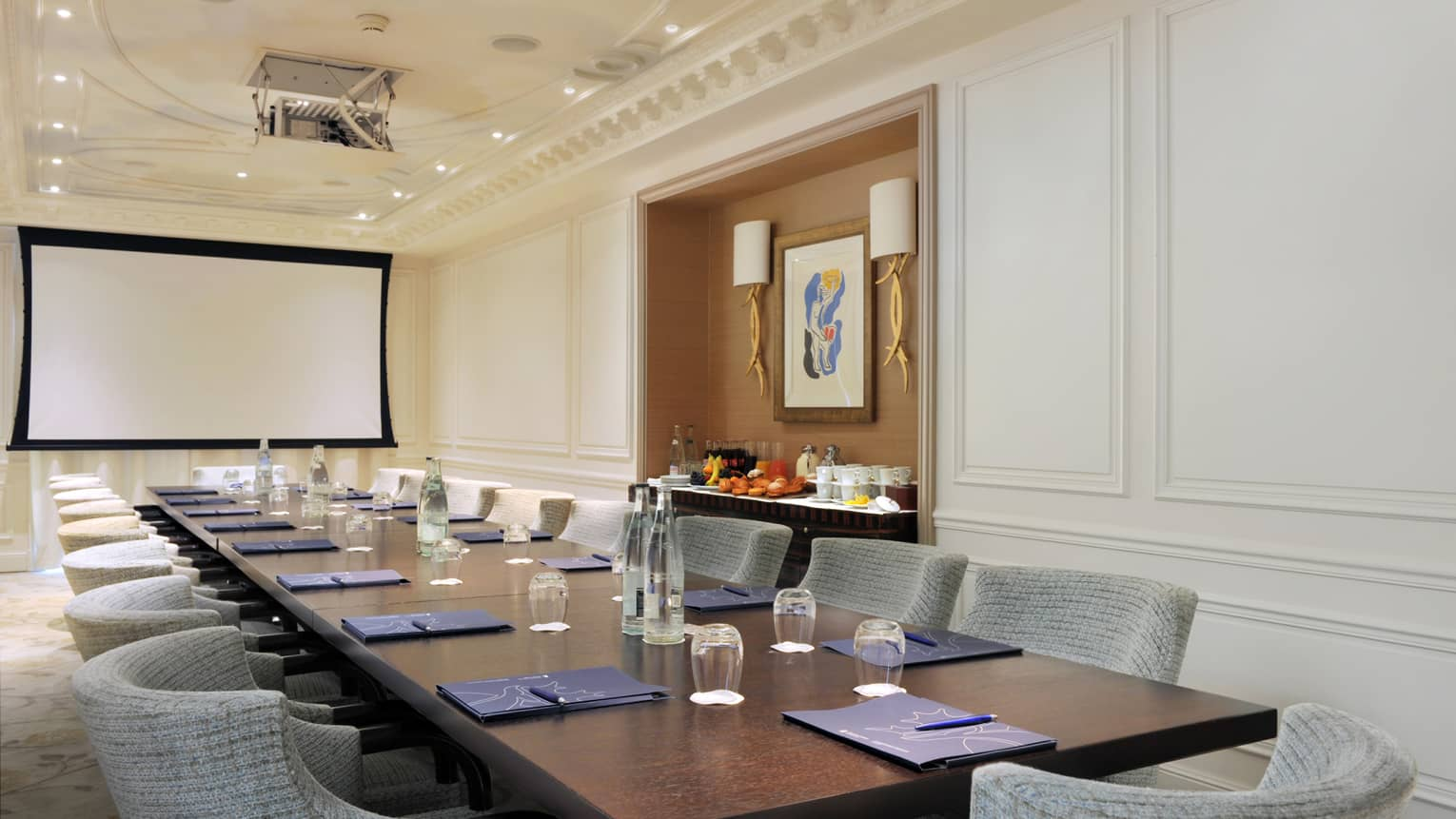 Salon le cap meeting room with grey chairs around large wood boardroom table, screen