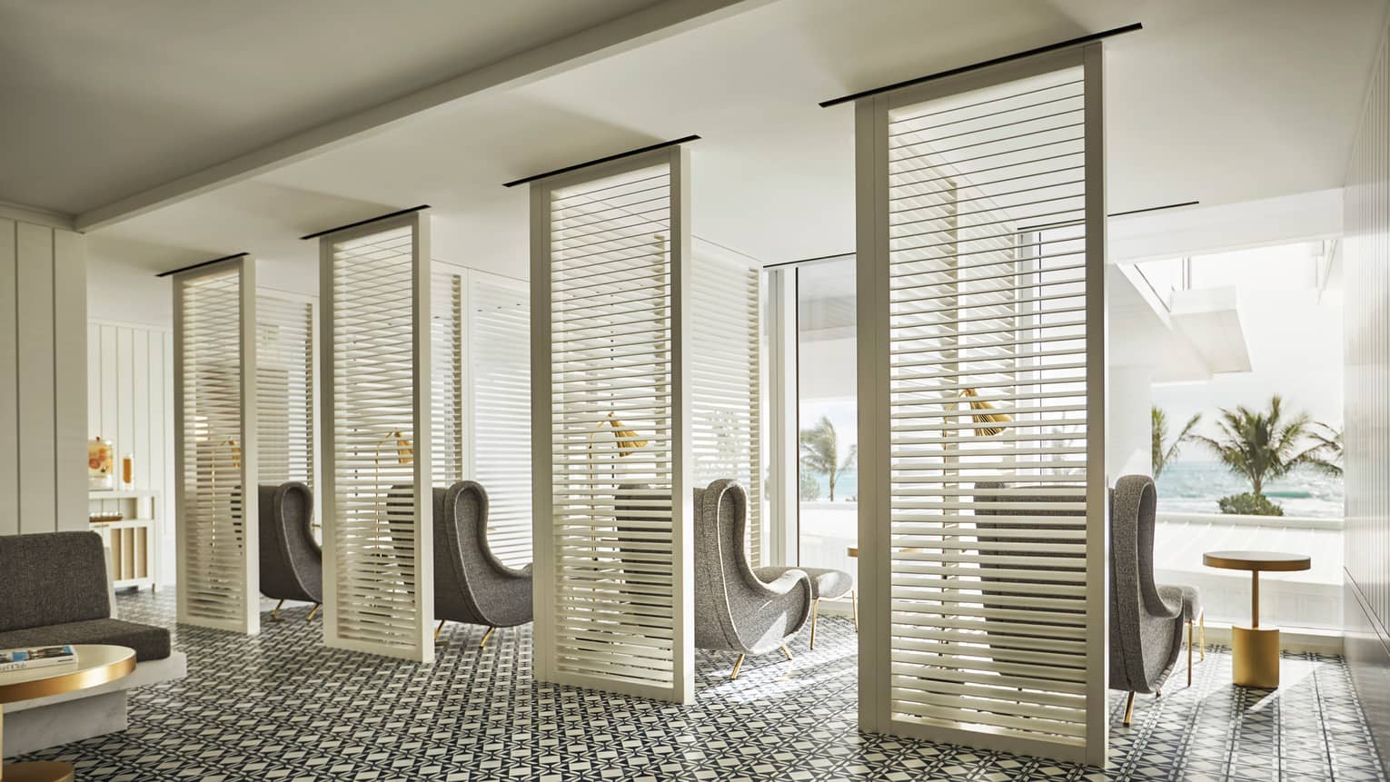 Oceanfront spa and wellness center. Retro-style grey arm chairs in front of window overlooking ocean