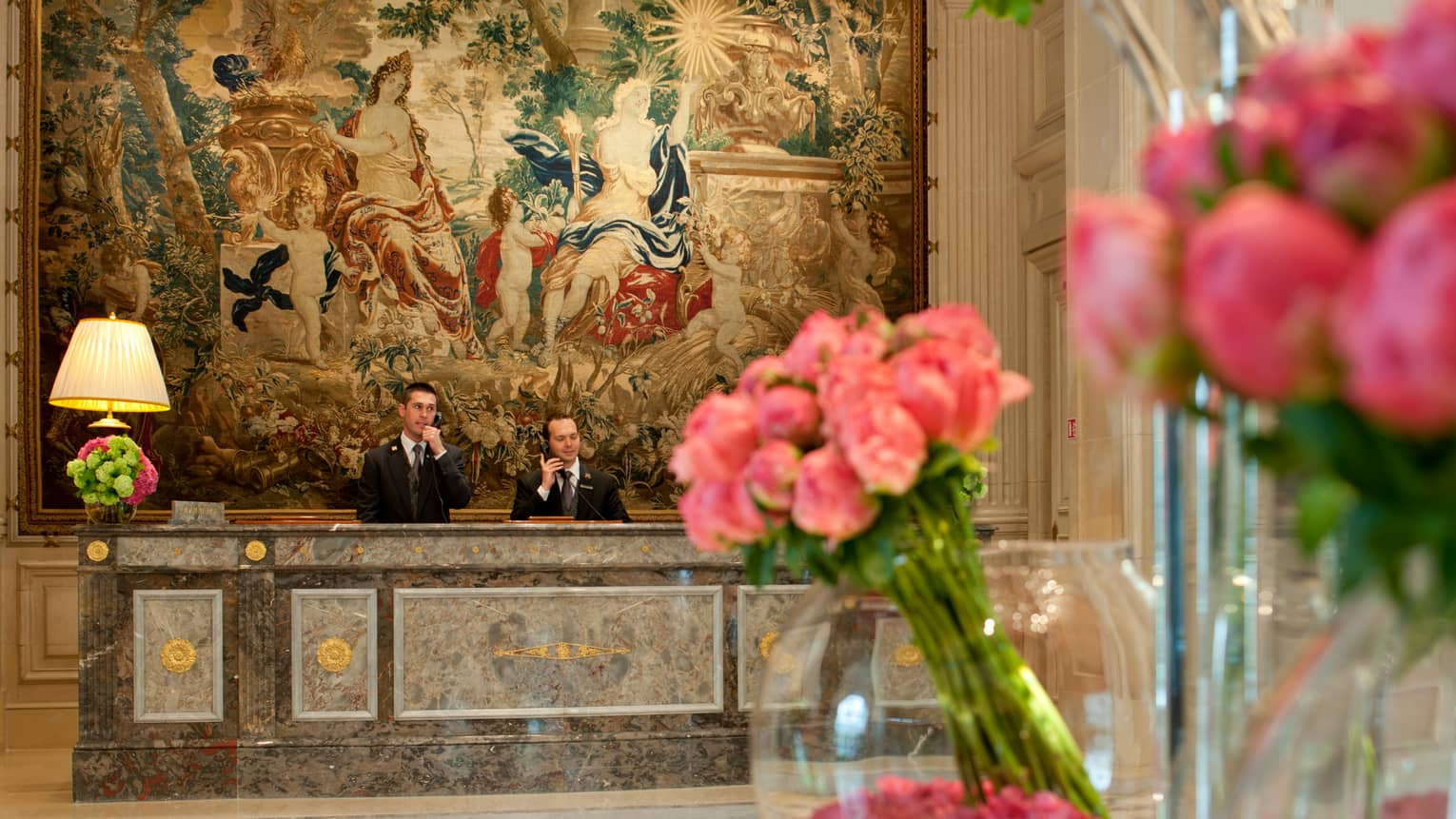 Hotel staff answer telephones at marble reception desk under large mural past pink flowers