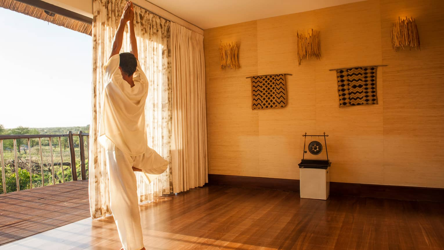 Woman in white linen outfit stands, balances in yoga pose
