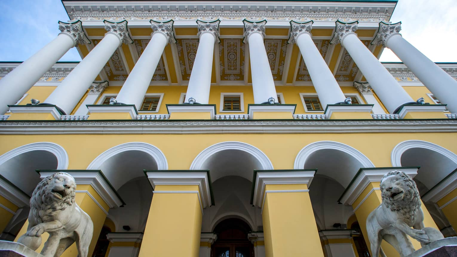Four Seasons Hotel St. Petersburg entrance looking up past two marble lions, tall white pillars