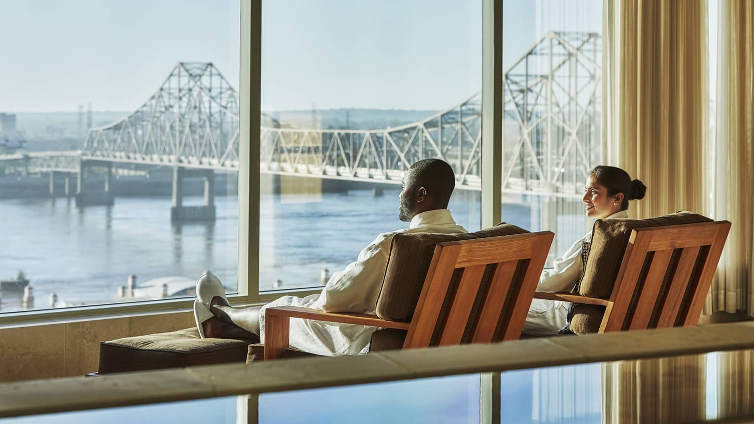 Couple lounge in chairs by large windows overlooking water, St. Louis bridge