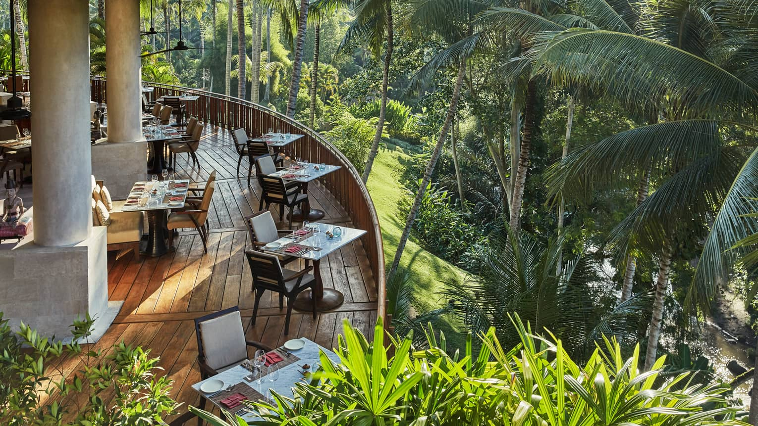 Looking down at curved wood patio of Ayung Terrace outdoor dining room, tables and chairs overlooking palm trees, forest