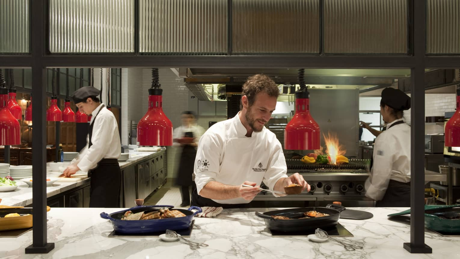 Chefs assemble dishes in a bustling kitchen, lit by red lights